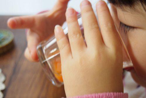 にんじんジュースを飲んでいる3歳児