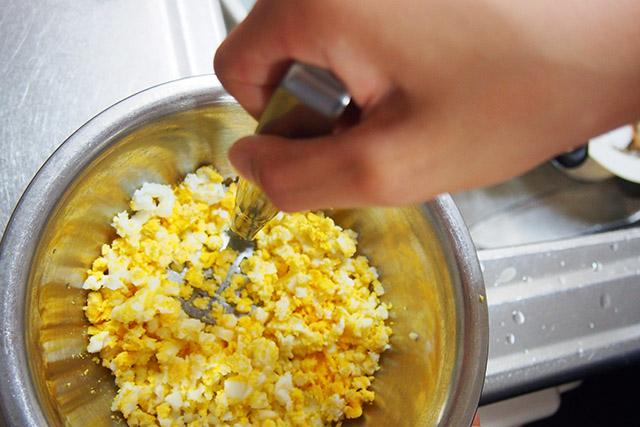 マッシャーでゆで卵を潰す