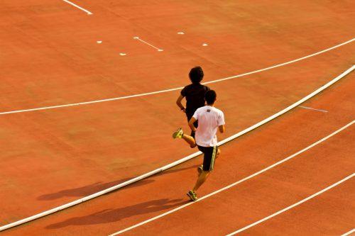 競技場のトラックを走る陸上の選手2人©:すしぱく